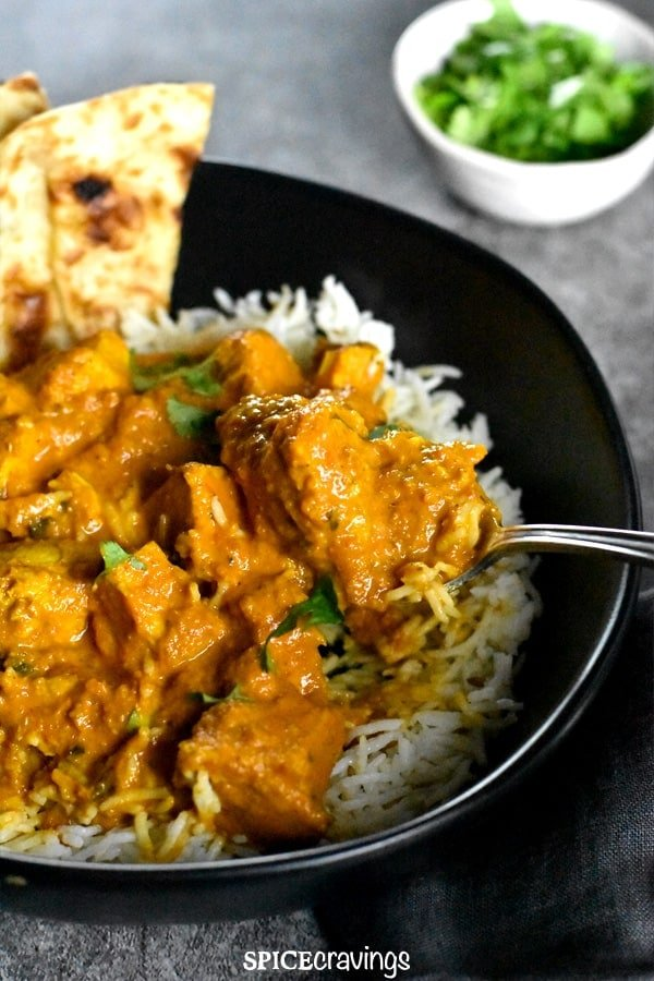 Chicken Tikka Masala served over rice in a black bowl