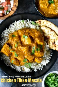 Chicken Tikka Masala served over a bowl of rice, paired with Garlic naan on the side