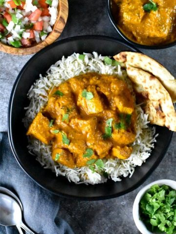 Tender juicy chicken tossed in tikka masala curry, served with rice and naan in a black bowl
