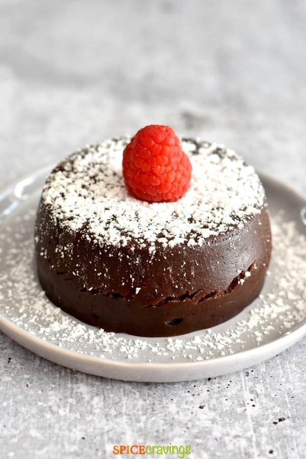 Chocolate cake topped with raspberry and powder sugar