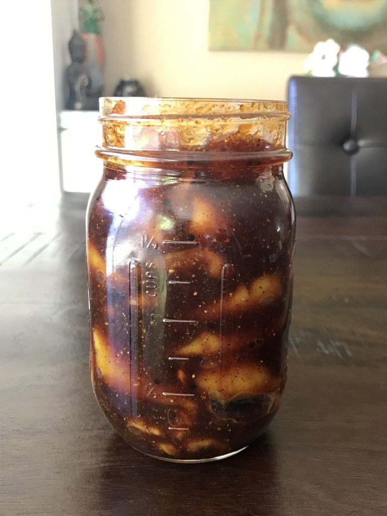 A jar of Indian spiced lemon pickle on a table