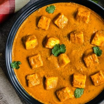 Cubes of paneer in tomato curry garnished with cilantro leaves