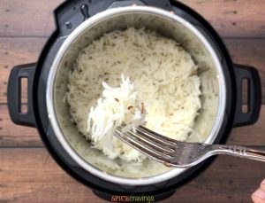 forkful of cumin rice held over instant pot