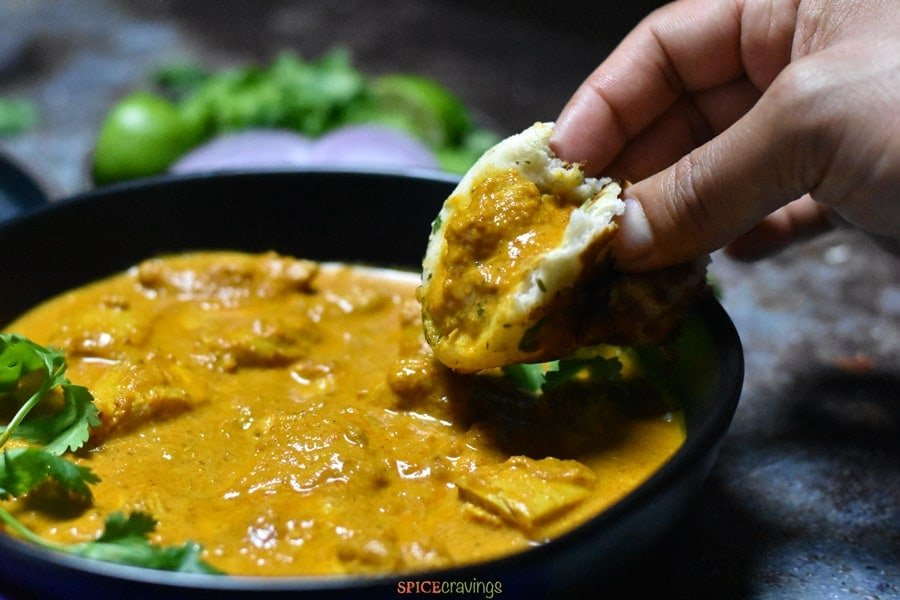Using Naan to scoop a bite of a Authentic Butter Chicken