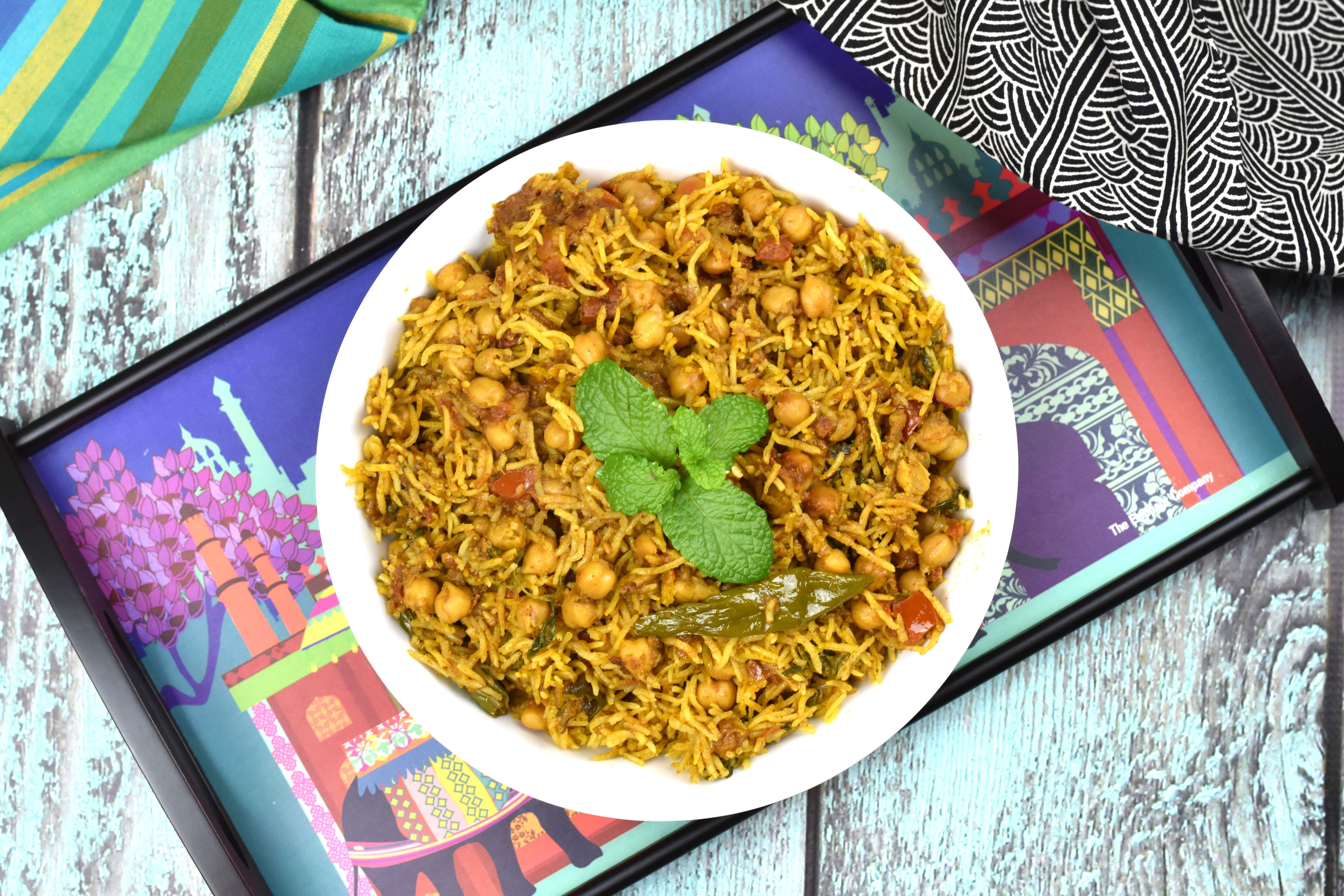 A chickpeas and rice pilaf served in a white bowl on a colorful tray.