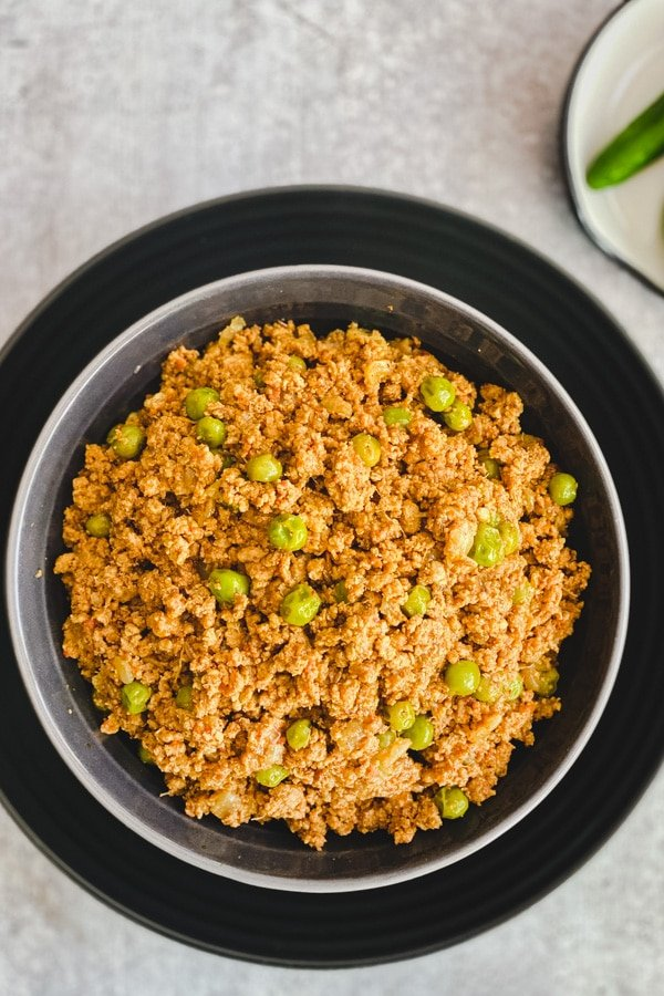 Indian spiced ground meat and peas in a copper bowl