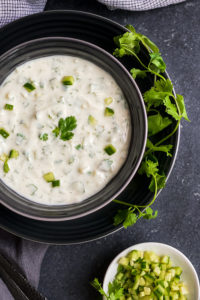 Indian yogurt dip called Raita, made with chopped cucumber and yogurt and garnished with mint.