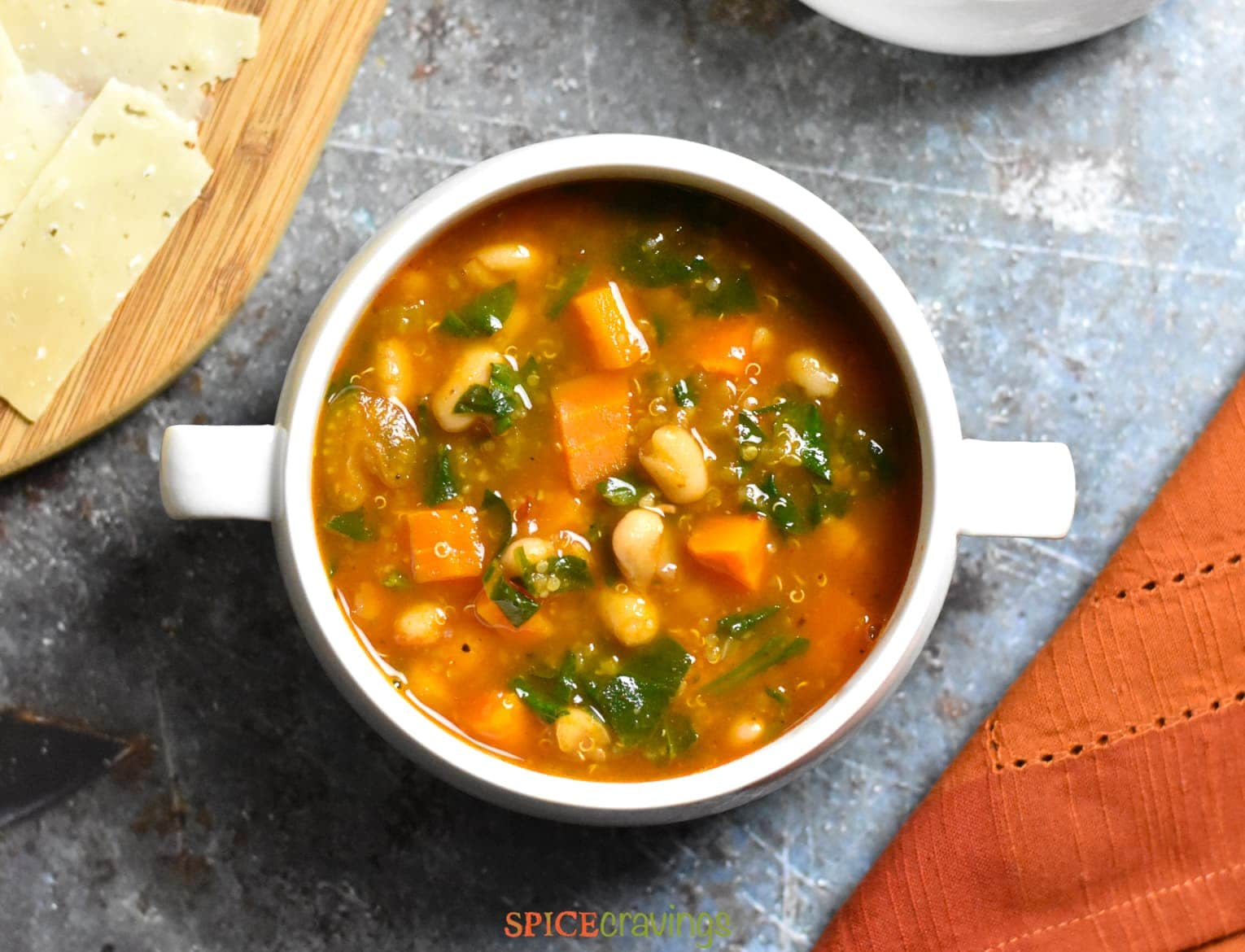 White bowl with Instant Pot Minestrone Soup with cheese board on side