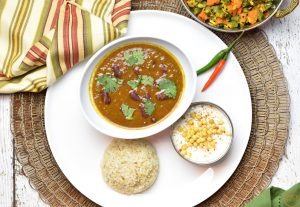 Rajma Chawal or kidney beans and rice, and boondi ka raita served on a white plate