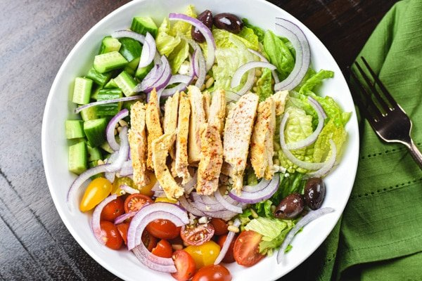 sliced chicken over greek salad in white bowl