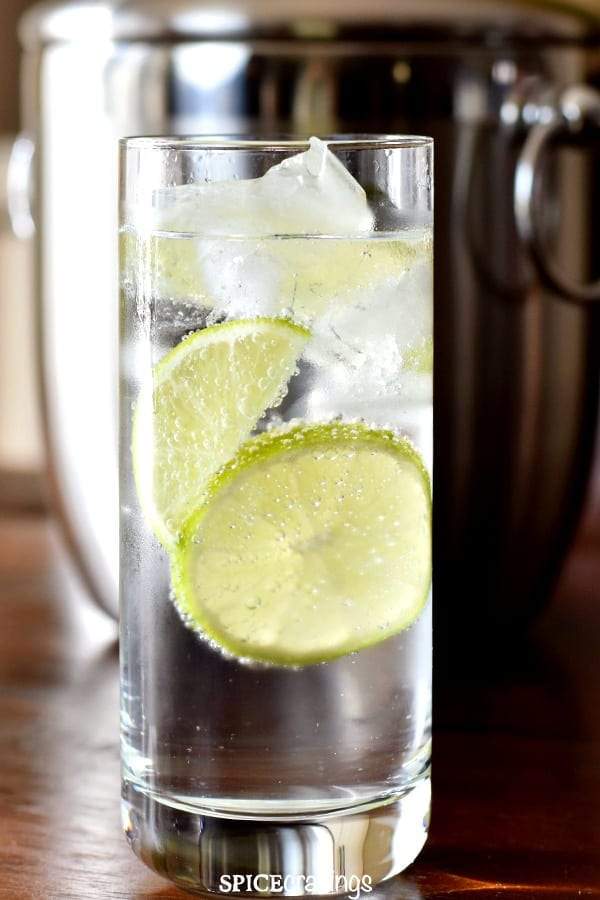 A tall glass of gin tonic served with ice and lime slices