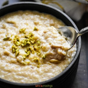 Bowl of Indian rice pudding garnished with chopped pistachios