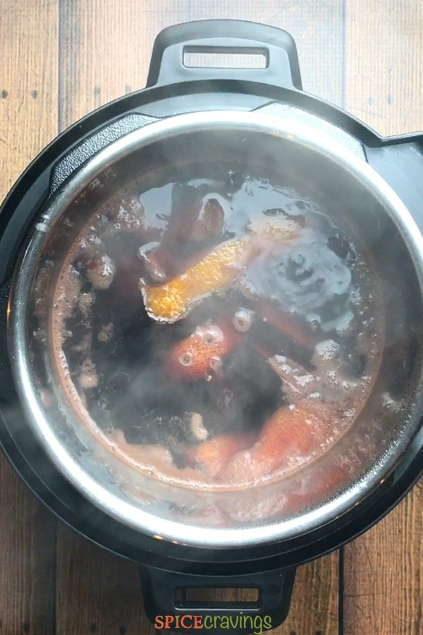 A pot of mulled wine simmering with citrus and spices