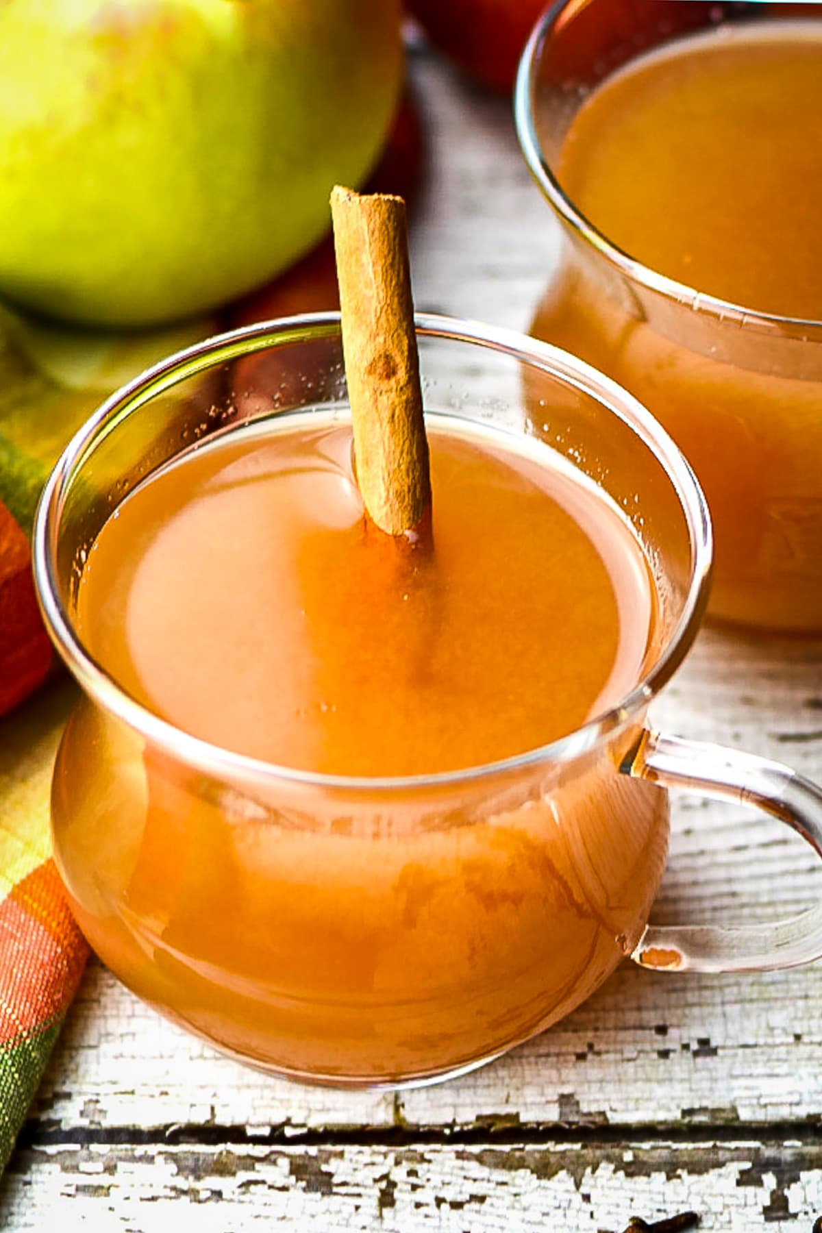 Spiced apple cider served in cups with cinnamon stick