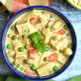 Thai green curry with vegetables and Tofu served in a blue bowl