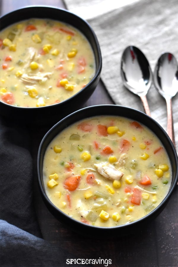 Chunks of chicken, carrots, potatoes and corn in two bowls of chicken corn chowder
