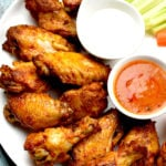 Crispy chicken wings on a plate with hot sauce and ranch