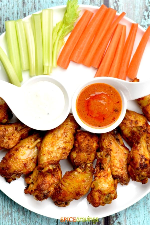 A plate of crispy chicken wings served with hot sauce, ranch and veggies