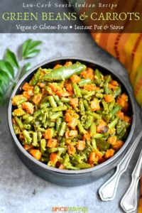 Green Beans and Carrots served in a black bowl with curry leaves on the side