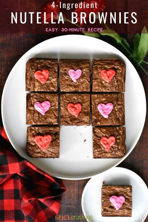 Chocolate brownies decorated with pink and red hearts on a white plate