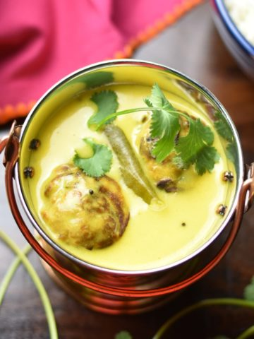 Punjabi kadhi or Yogurt curry with onion-spinach fritters served in a fancy container