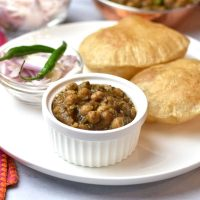 Indian spiced chickpeas curry called chole, served with a puffed bread called bhatura