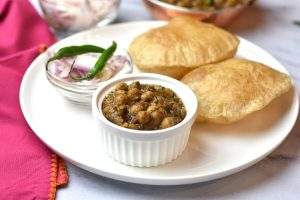 Chole Bhature or chickpea curry served with fried flatbread and a side of onions on a white plate.