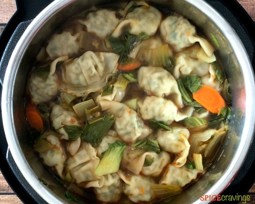 Cooked wontons floating to the top of the soup