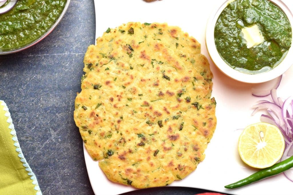 Makki Ki Roti, seasoned cornmeal flatbread, served with spiced mustard greens called Sarson Ka Saag, on a white plate