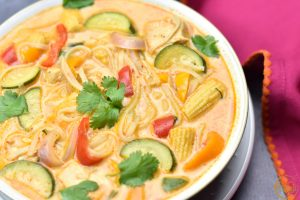 Close-up of Thai Red Curry Soup with noodles, baby corn, and zucchini in a bowl