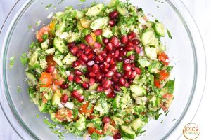 mixed quinoa tabbouleh salad in glass bowl with pomegranate seeds