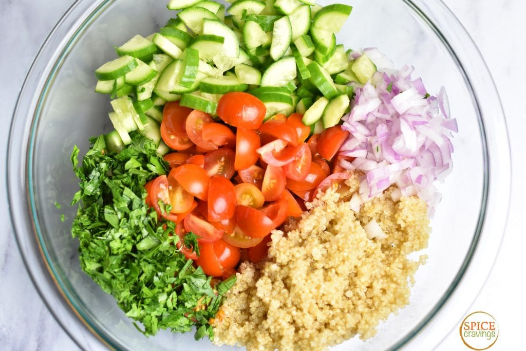 quinoa, red onion, tomatoes, cucumber, herbs in bowl