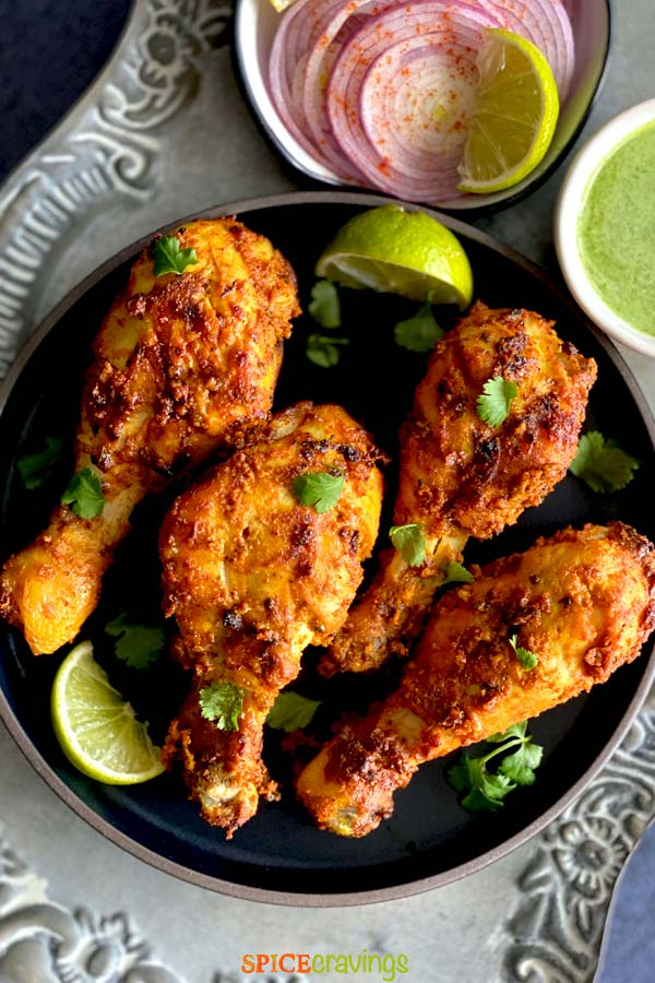 tandoori chicken legs on black plate with pickled onions and cilantro chutney