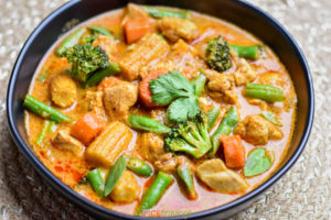 Thai Massaman curry with baby corn, broccoli, green beans, and chicken in a blue bowl