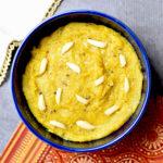 Badam halwa garnished with slivered almonds, served in a blue bowl