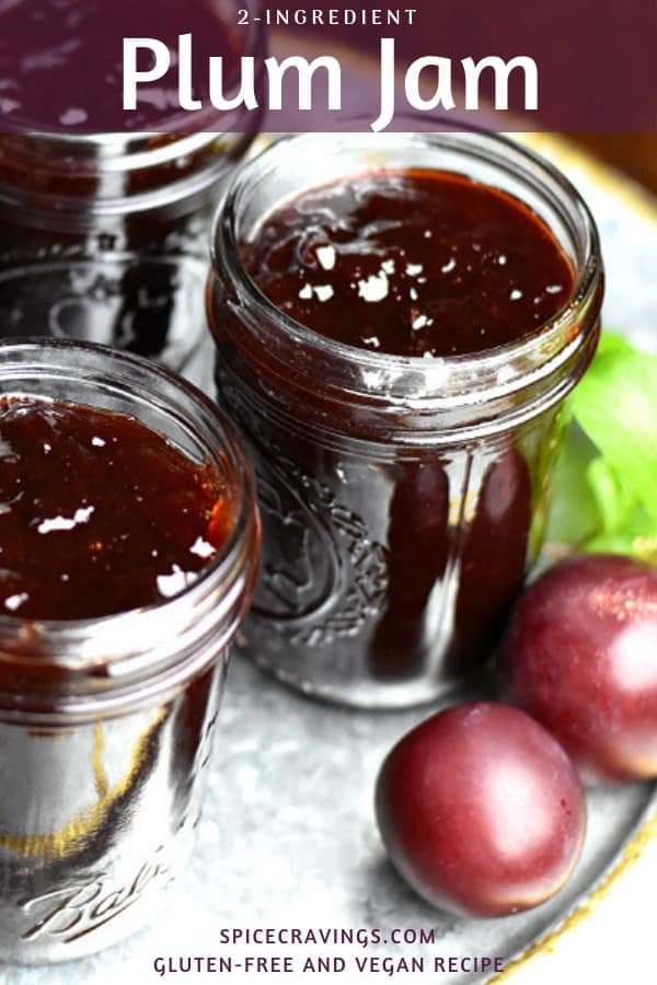 Jars of plum jam placed next to some fresh plums