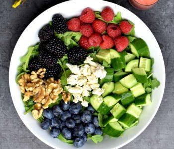 arugula, cucumbers, raspberries, blueberries, blackberries, walnuts, feta in white bowl with two spoons