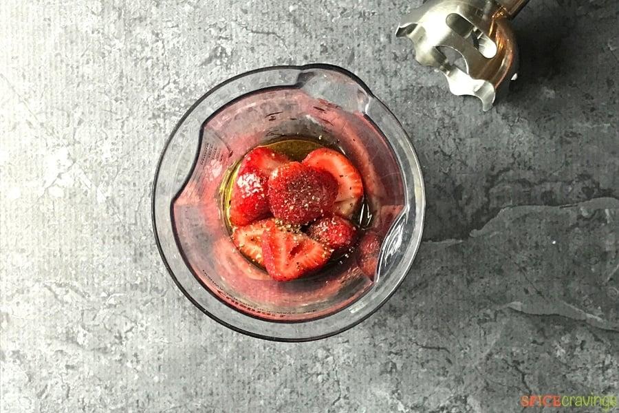 Cut strawberries, black pepper, oil and vinegar in a blender jar