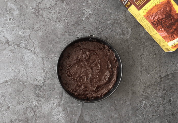 Brownie batter spread evenly in a cake pan
