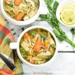 Two bowls of chicken noodle soup placed on aa blue wooden background