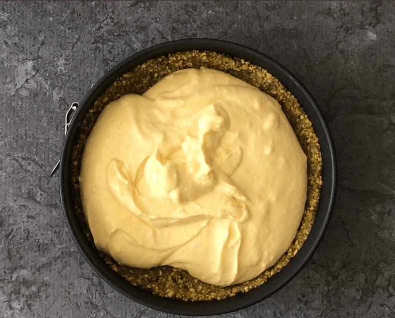Mango cheesecake filling on a pistachio crumb crust