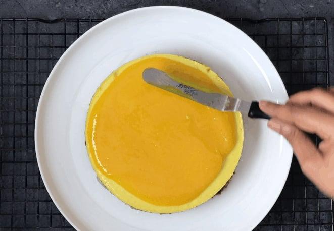 Spreading mango topping on Mango cheesecake