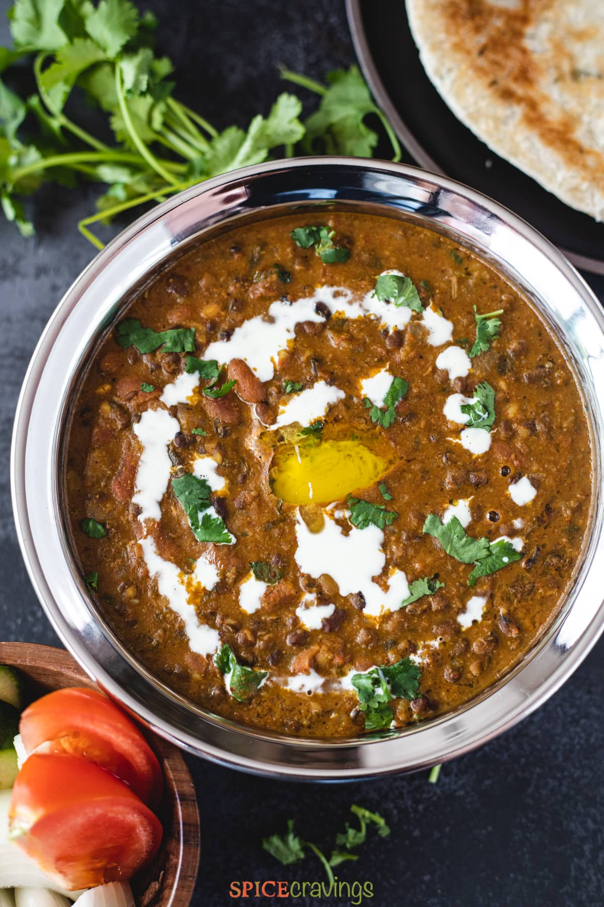 Easy Dal Makhani served in a black bowl with side of naan