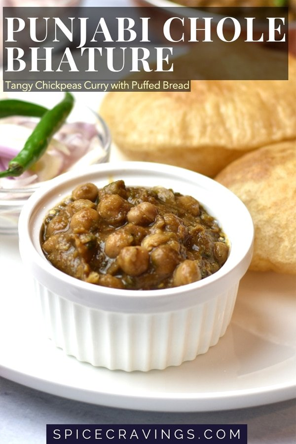 Punjabi Chole Bhature, Spiced chickpeas curry is served with a deep fried puffed bread on a white plate