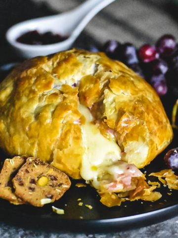 Brie cheese melting out of the puff pastry dome- baked brie recipe
