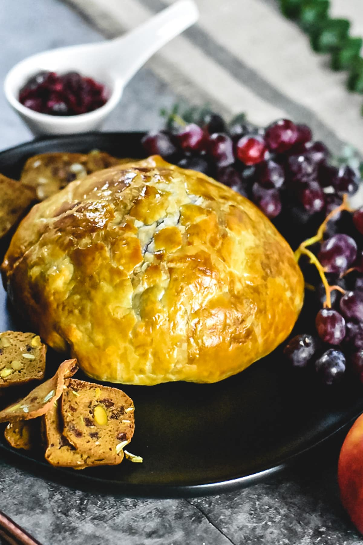 Baked brie in puff pastry served on a black plate with grapes and crackers, jam in the background