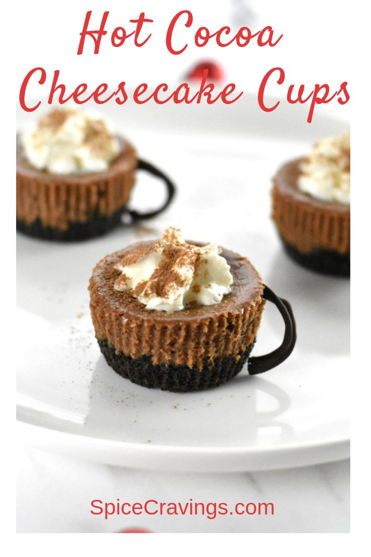 Hot cocoa flavored mini cheesecakes with chocolate handles, & topped with whipped cream.  This Hot Cocoa Cheesecake Recipe is the best of both worlds! #spicecravings #cheesecake #chocolate #dessert #cocoa
