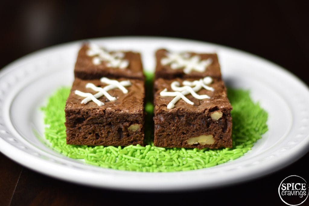 Fudgy chewy brownies on a white plate with green sprinkles