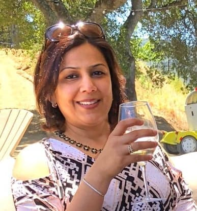Aneesha holding a glass of white wine