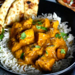 A bowl of chicken tikka masala served with cumin rice and naan